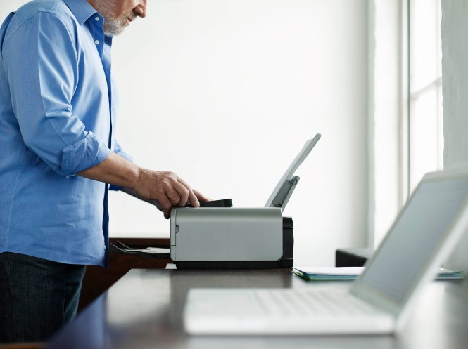 Man Using Printer At Study Table In House